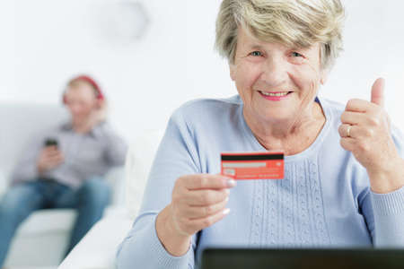 senior woman: Happy senior woman with her thumb up, holding debit card, in the background blurred image of a young man
