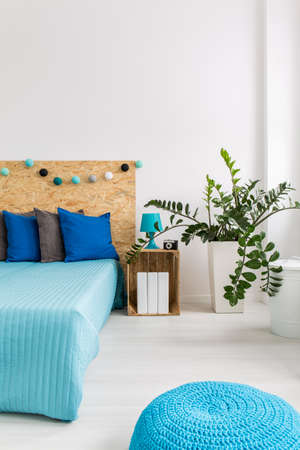 pouffe: Light bedroom with double bed, plant and blue pouffe