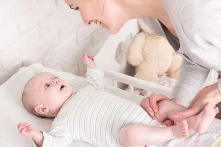 diaper changing table: Happy young mother bending above her little baby in sleepers lying  on a changing table. Preparing baby to change a diaper