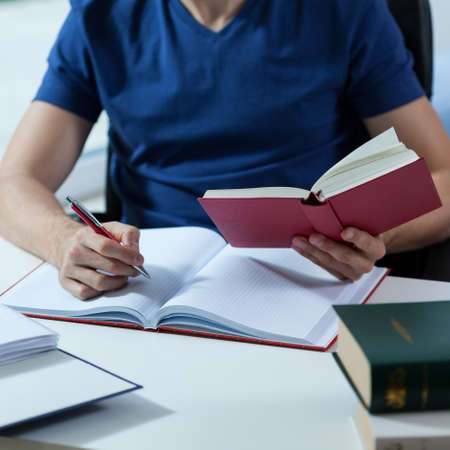 researches: Male student transcribing the notes from the book in library