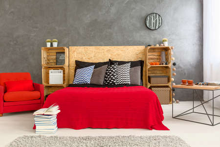 gray: Modern designed bedroom with red bed and armchair on the background grey wall. Wooden shelves made of wooden boxes and wooden headboard to the bed