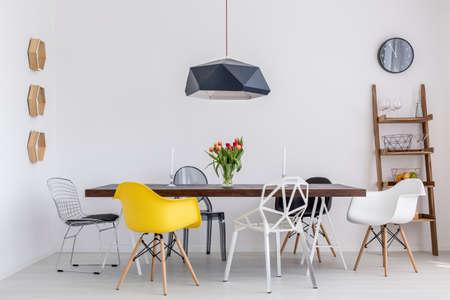 Záběr kreativní jídelny s velkým stolem a šesti různých židlí Reklamní fotografie