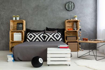 Spaziosa camera da letto up-to-date con le pareti grigie, letto matrimoniale e ripiani in scatole di legno. Di fronte a letto bianco tavolino in legno