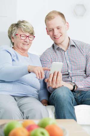 persona de la tercera edad: Hombre joven que enseña a su abuela cómo utilizar el smartphone Foto de archivo
