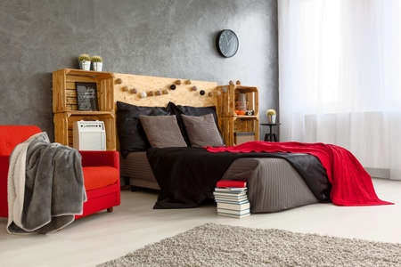 red bed: Modern stylish design of spacious bedroom. Grey walls and grey and red bed with wooden shelves on the both side Stock Photo