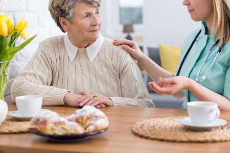 Senior dame assise à une table avec son infirmière à domicile, parler ensemble et manger du gâteau