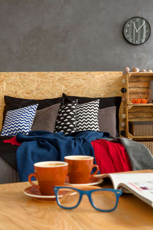 coffee table: Wooden coffee table with two cups with coffee and blue glasses. In the background double bed with pillows Stock Photo