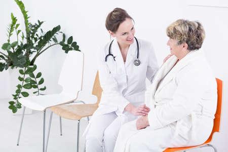 Shot van een jonge arts die met haar senior patiënt praat Stockfoto