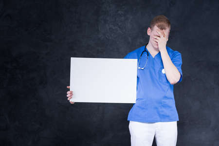 face expressions: Young red-haired doctor holding a large white sheet of paper, hiding his face in his hand as a display of frustration