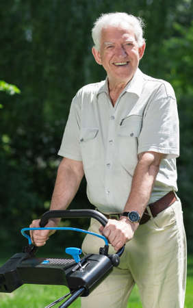 closer: Closer shot of an older man standing with the lawnmower in his garden and smiling