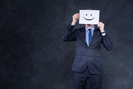 happy workers: Shot of a smartly-dressed man who is hiding his face behind a white page with happy emoticon printed on it Stock Photo