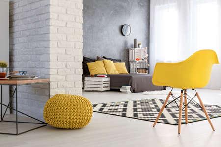 Prostorná ložnice s bílou cihlovou zeď. Dřevěný konferenční stolek a žlutá židle. U zdi šedé posteli s žlutými polštáři
