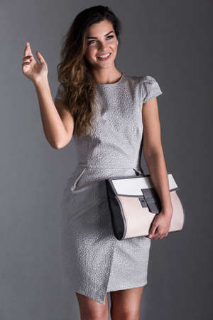 clutch bag: Young woman holding a large clutch bag and waving with a smile Stock Photo