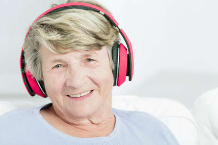 new age music: Portrait of a happy senior woman with pink headphones, light background