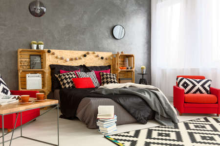 red pillows: Grey spacious bedroom with big bed with grey and black blankets and red pillows. Next to it red armchairs and wooden coffee table Stock Photo