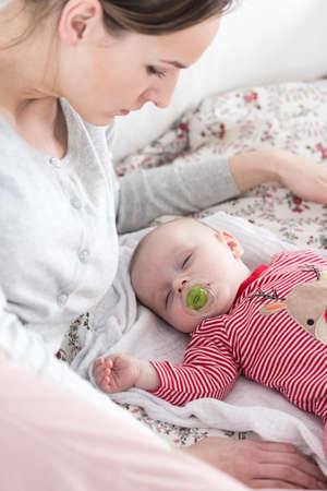teat: Little cute baby with teat in mouth sleeping on a bed. Next to him watching young careful mother Stock Photo