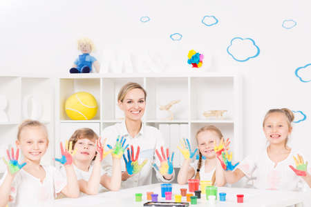 painted hands: Shot of a group of children and a teacher showing their painted hands to the camera