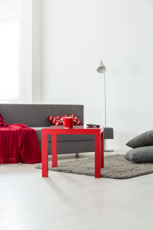 panelled: Sofa corner of a very bright flat, with a red coffee table and fluffy carpet