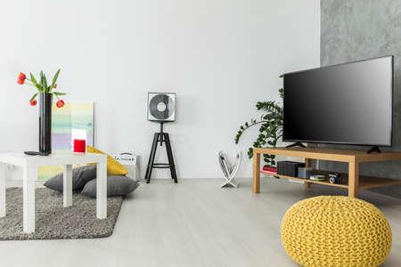 Moderna sala de estar con un mobiliario sencillo pero a la moda y un aparato de TV, dispuestos en gris y amarillo Foto de archivo