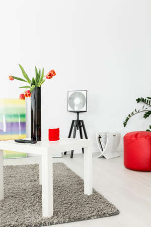 Fragment of a very bright modern living room, with a white coffee table with tulips in a vase
