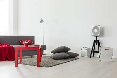 panelled: Minimalist interior of a bright living room with a grey sofa, red coffee table and a pile of cushions