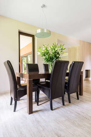 dining table and chairs: Shot of a modern dining room with a wooden table and chairs