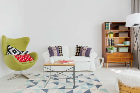 modernist: Interesting lounge room with a cozy sofa, green egg chair and modernist bookcase Stock Photo