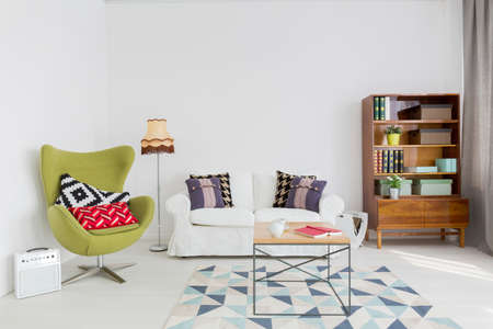 Very bright living room with white walls and floor, renovated modernist furniture and a green egg chair