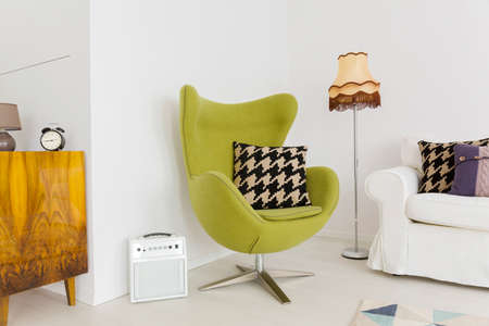 modern chair: Lounge corner of a modern apartment with a cosy swivel egg chair Stock Photo