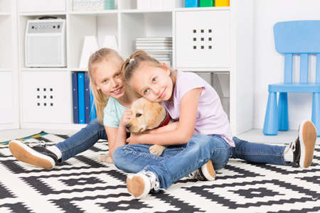 two girls hugging: Shot of two girls hugging a puppy in their room