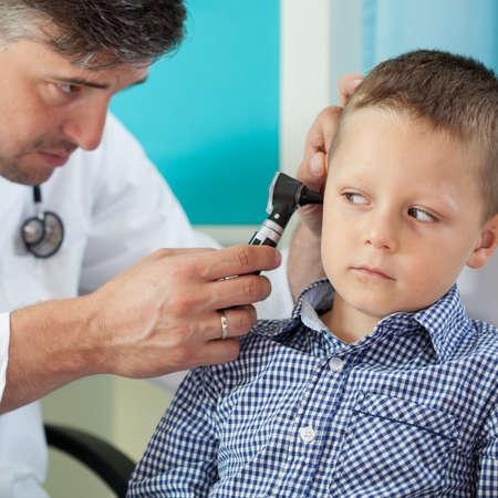 examine: Pediatrician using otoscope to examine boys ear Stock Photo