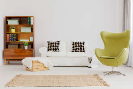 renovated: Harmonious and elegant living room decor, with a renovated modernist bookcase and a green egg chair