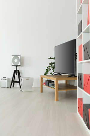 panelled: Tv corner of a modern flat, with a flat tv on a wooden rack standing on white panelled floor Stock Photo
