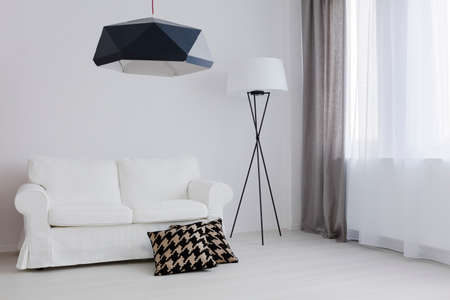 white interior: Very bright room arranged in black and white, with a comfortable sofa and decorative pillows Stock Photo