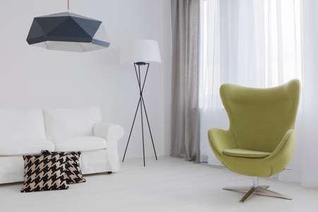 Fragment van een zeer lichte woonkamer met een groene ei stoel en een comfortabele bank