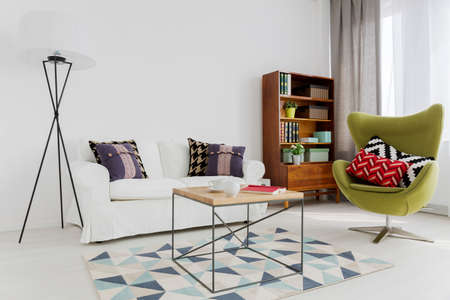 coffee table: Room corner of a modern flat, with a designer swivel armchair and a modernist bookcase
