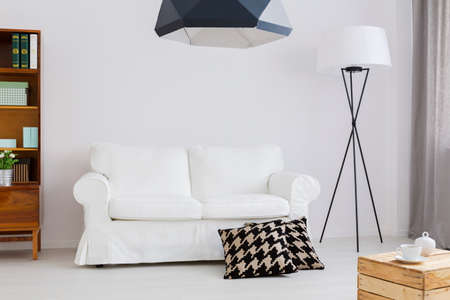 White comfortable sofa with two decorative pillows in a very bright apartment