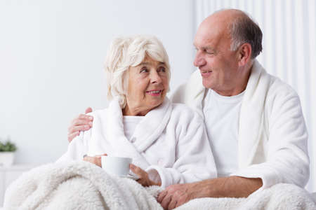 senility: Older happy man embraces his wife in the morning