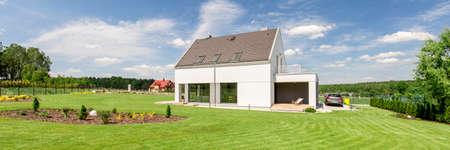 Panorama-Foto von einem modernen weißen Einfamilienhaus auf dem Land, umgeben von Ebenen und Wälder