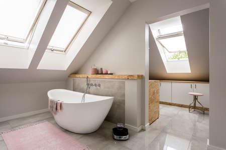 새로운 대형 욕조가있는 넓은 가벼운 다락방 욕실 스톡 콘텐츠