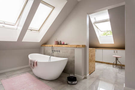 Spacious light attic bathroom with new large bathtub Stok Fotoğraf