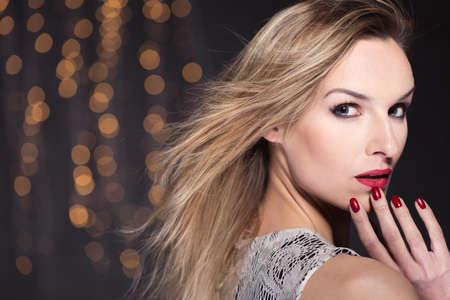 uñas largas: Retrato de una mujer elegante en maquillaje completo mirando sobre su hombro a la cámara