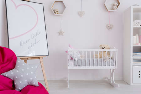 room: Fragment of a little girls room with a white cradle and a picture frame on an easel with a cute printout
