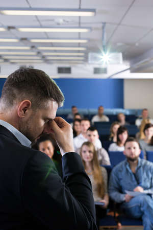 lecture theatre: Miserably looking young academic teacher holding his forehead as if he had a headache, in a room full of students
