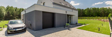 Modern garage joined with a detached house in the country, with cobbled driveway in the first ground Stock Photo