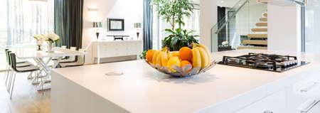 Velmi elegantní a prostorný interiér domu s bílou kuchyňský ostrůvek v popředí