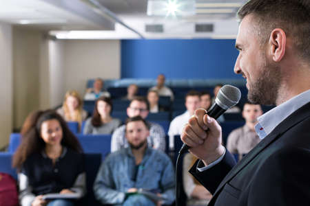 smartly: Close-up of a smiling teacher with a microphone, talking to a group of students in a lecture hall Stock Photo