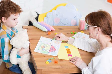 Dětský psycholog ukazuje výkres domu na malého chlapce s křížovou výrazem ve tváři, který drží bílý medvídek