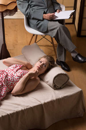psychoanalysis: Depressed woman is lying on a psychiatrist couch and wondering about something