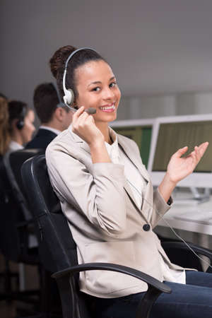 professionalist: Young female consultant sitting on a chair and explaining something to the client by telephone Stock Photo